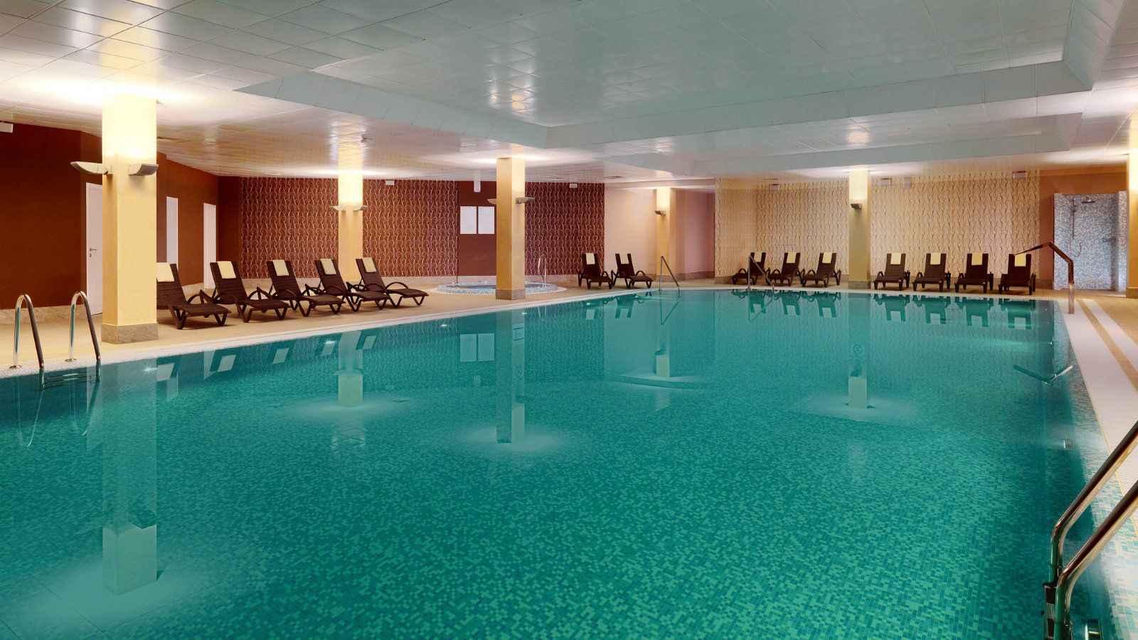 Spacious swimming pool with comfortable lounge chairs for relaxing at Sheraton Moscow Sheremetyevo